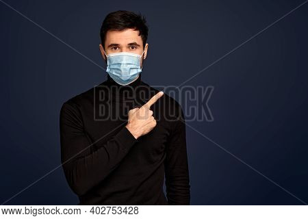 Young Man In Sterile Face Mask Pointing Index Finger Aside Isolated On Pacific Blue Background. Epid
