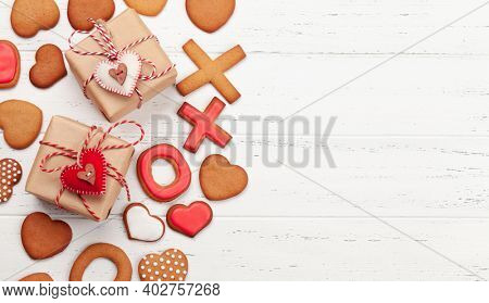 Valentines day concept greeting card with gingerbread cookies and gift boxes. Top view flat lay with copy space