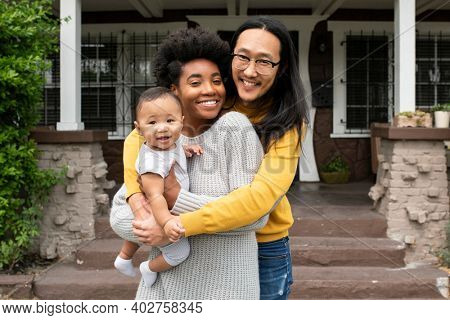 Cute multiethnic family standing at the porch during covid19 lockdown
