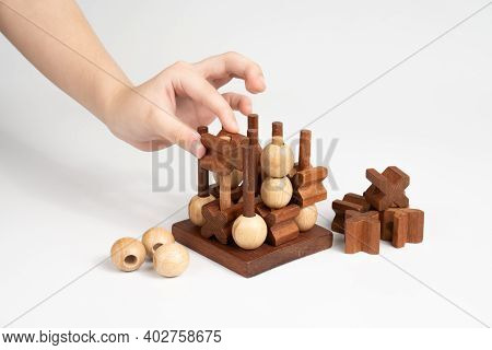 The Child Makes A Move In The Game Of Tic-tac-toe. Three-dimensional Wooden Voluminous Field For Tic