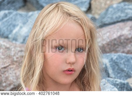 Portrait Of A Little Girl Of Five Years Old, Blonde, Blue Eyes, With A Pensive Look