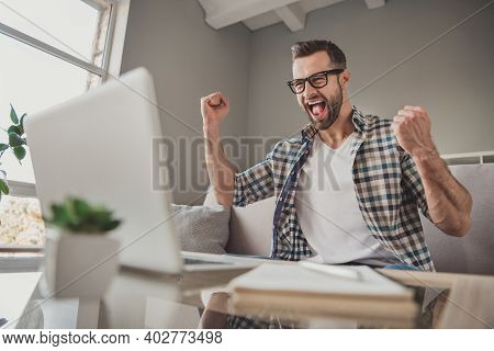 Photo Of Young Excited Man Happy Positive Smile Celebrate Win Victory Success Fists Hands Sit Sofa H