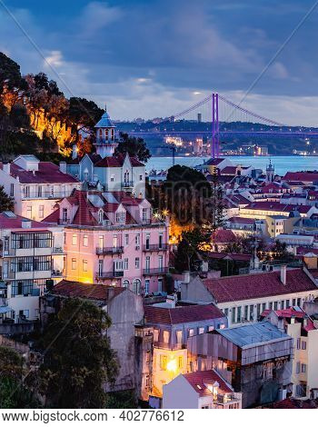 Cityscape Of Lisbon At Dusk With Traditional Historical Houses And The 25 Ponte De Abril Bridge Over