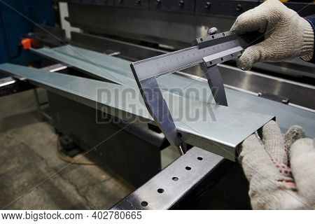 A Specialist At The Factory Measures The Accuracy Of Bending Of  Metal Sheet Used As A Cover For An