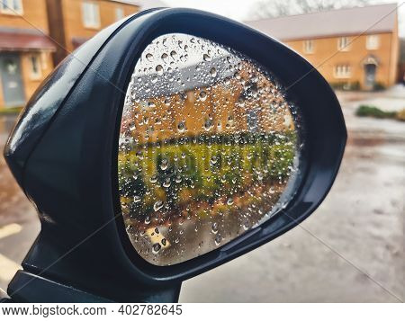 Rain Drops And A View Of A Newly Built Neighborhood Seen In The Wing Mirror Of A Car