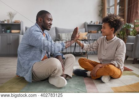 Joyful Father And His Teen Son Spending Time At Home Sitting On Floor In Living Room Playing Clappin