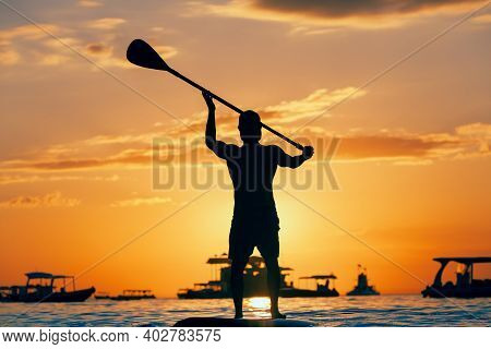 Active Paddle Boarder. Black Sunset Silhouette Of Young Sportsman Paddling On Stand Up Paddleboard.