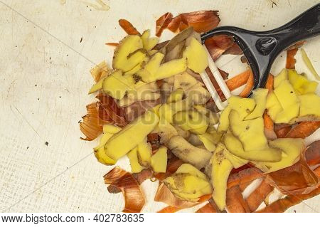 Carrot And Potato Peel And Onion Peel With Peeler On White Board Close-up