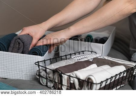 Vertical Storage Of Clothing.women Organize Clothes In A Modern Bedroom. Women Sorting Clothes In Ba