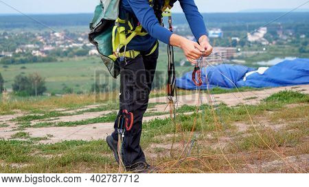 Male Parachutst Folding And Preparing His Parachute Before Jump. Concept Of Extreme Sport And Adrena