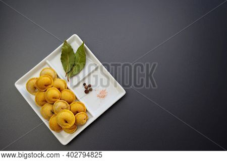 Yellow Frozen Homemade Dumplings And Spices In A Square Plate On A Gray Background. Homemade Semi-fi