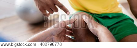 Cropped View Of Injured African American Sportsman Pointing With Finger At Knee Near Chiropractor, B