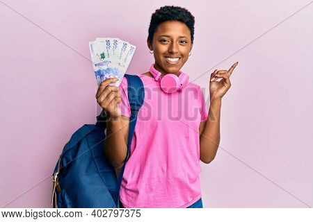 Young african american girl wearing student backpack holding colombian pesos banknotes smiling happy pointing with hand and finger to the side
