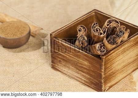 Cinnamon Powder And Cinnamon Stick; Photo On Wooden Background.