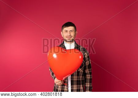 Portrait Of A Young Brunette Guy Looking To Camera, Holding A Heart-shaped Balloon On A Red Backgrou