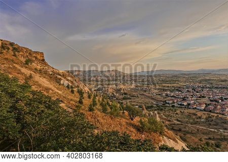 Cappadocia Landscape At Golden Hour. In The Foreground Is A Mountain Slope With Coniferous And Decid