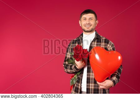 Man With A Bouquet Of Red Roses And A Red Heart-shaped Balloon On A Red Background With Side Space.