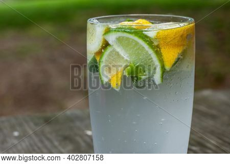 Glass with sparkling water and lemons outside