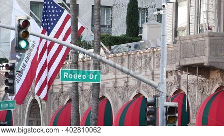 World Famous Rodeo Drive Street Road Sign In Beverly Hills Against American Unated States Flag. Los