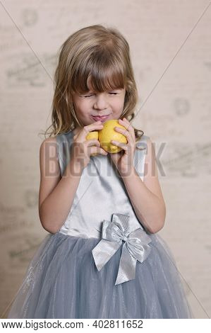 Little Blond Baby Girl Eating Sore Lemon And Grimacing On Retro Wall Interior Background