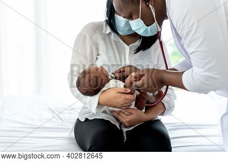 African Doctor Wearing Surgical Mans And Using A Stethoscope, Checking The Respiratory System And He