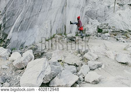 Extraction Of Blue Marble In Karelia. A Woman In A Red Hat And With A Red Bag Stands At A Marble Min