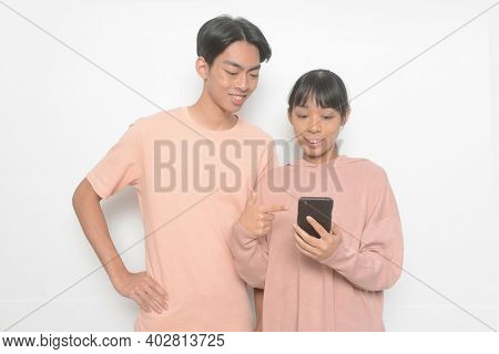 young couple. Man and woman in love in casual clothes, jeans standing using and texting on their mobile smart phones isolated on white background.