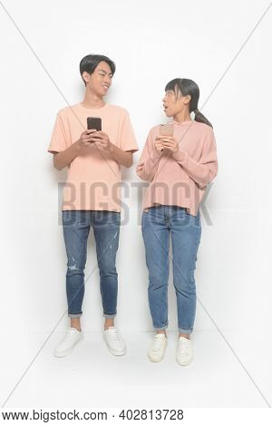 young couple. Full body man and woman in love in casual clothes, jeans standing using and texting on their mobile smart phones isolated on white background.