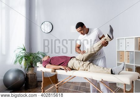 African American Chiropractor Working With Middle Aged Man In Modern Clinic