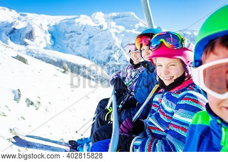 Happy Smiling Group Of Children Sit On Chairlift And Looking At Camera Over Sunny Mountain Peaks On