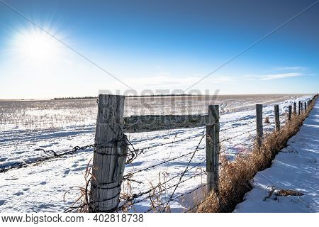 A Barbed Wire Fence With Fence Posts On The Canadian Prairies In Rocky View County Alberta Canada.