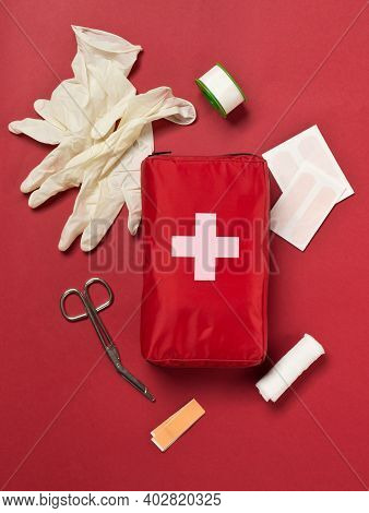 Red First Aid Medical Kit Bag With Scissors, Tape And Gloves Top View Flat Lay From Above Over Red B