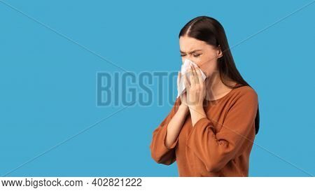 Cold And Flu. Sick Woman Blowing Runny Nose In Paper Tissue Having Rhinitis Symptom Standing On Blue