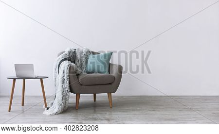 Minimalist Home Workspace Design. Modern Armchair With Blue Pillow And Soft Plaid, Next To Small Tab
