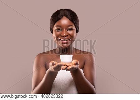 Skin Nourishing. Attractive Black Woman Holding Jar With Moisturising Cream In Hands, Demonstrating