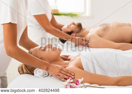 Relaxed Spouses Receiving Shoulders Massage Enjoying And Relaxing During Couples Beauty Therapy At L