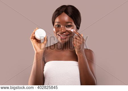 Skin Care. Smiling African Woman In Towel Applying Moisturizing Cream On Face, Holding Jar With Nour