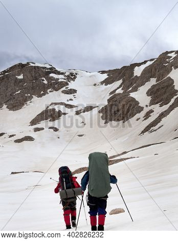 Two Hikers On Snowy Plateau In High Mountains Before Storm. Turkey, Central Taurus Mountains, Aladag
