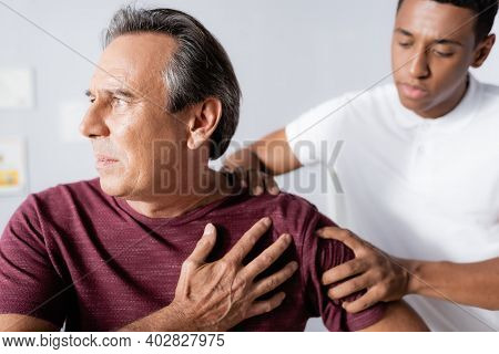African American Physiotherapist Working With Injured Mature Man In Clinic