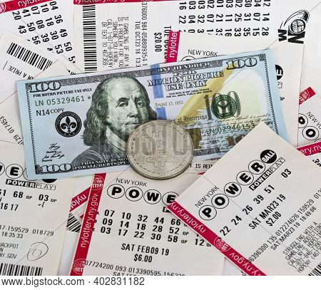Babylon, New York, Usa - 10 Janurary 2021: One Silver Bitcoin Coin On Top Of Lottery Tickets And One