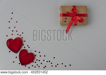 Two Red Transparant Heart And Little Sparkling Heart Confetti In Left Corner, Wrapped Giftbox Tired