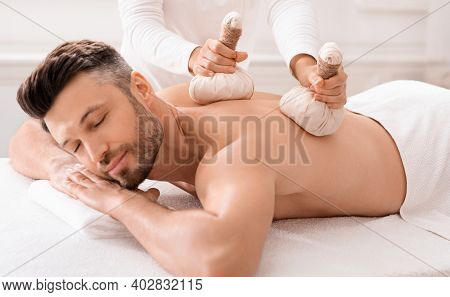Herbal Massage Concept. Unrecognizable Spa Attendant Making Body Massage For Handsome Man With Herba