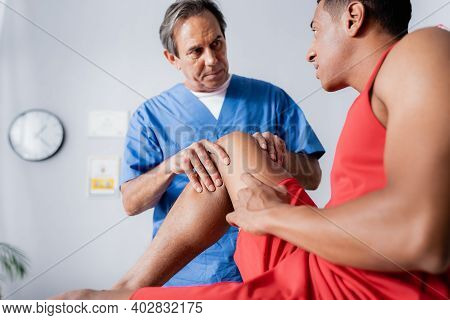 Mature Chiropractor Working With Injured Knee Of African American Man In Sportswear On Blurred Foreg