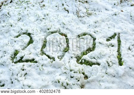 Number 2021 Written In The Thin Snow On The Lawn, So The Grass Becomes Visible, New Year Concept Or