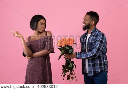 Irritated Black Woman Rejecting Geek Man Offering Flowers On Valentines Day Over Pink Studio Backgro