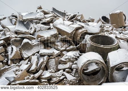 Heap Of Broken Concrete Drainage Pipes Under A Thin Layer Of Snow On A Construction Site, Waiting Fo