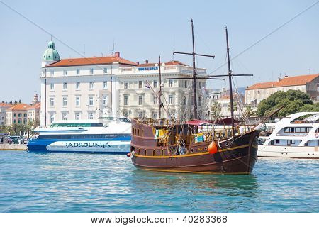 SPLIT, CROATIA - AUGUST 4, 2012: Galley and modern ship in Split harbor on August 4, 2012 in Split, Croatia. Split is the second-largest city of Croatia.