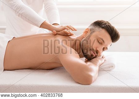 Side View Of Relaxed Handsome Man Having Body Massage At Spa Salon. Middle Aged Bearded Man Attendin