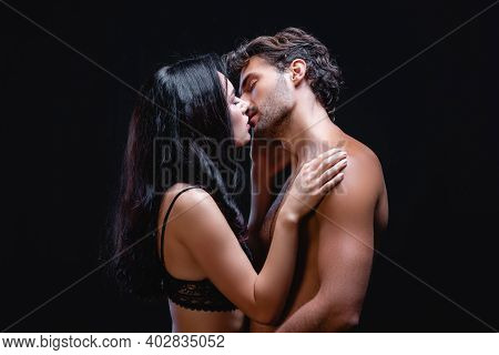 Side View Of Seductive Brunette Woman Kissing Sexy Shirtless Man Isolated On Black