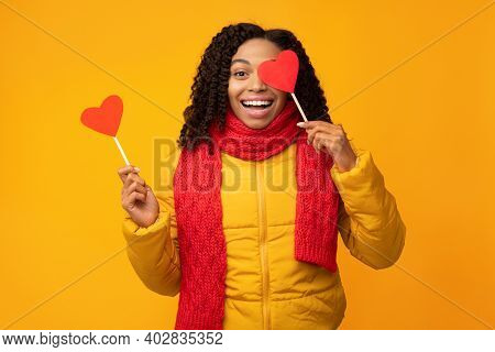 Valentines Day. Black Woman Posing With Paper Hearts Having Fun Covering Eye With Heart, Smiling To